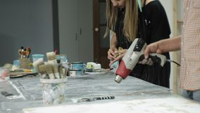 Os mestres no estúdio da arte processam a madeira com pintura e a massa de vidraceiro, consegue o efeito do envelhecimento vídeos de arquivo
