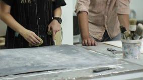 Os mestres no estúdio da arte processam a madeira com pintura e a massa de vidraceiro, consegue o efeito do envelhecimento filme