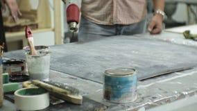 Os mestres no estúdio da arte processam a madeira com pintura e a massa de vidraceiro, consegue o efeito do envelhecimento video estoque