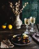 Os mexilhões cozinhados com shell serviram na placa com dois vidros do vinho branco Fotos de Stock