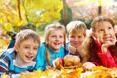 Os miúdos agrupam no parque do outono Imagem de Stock