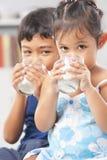 Os miúdos apreciam o leite bebendo fotos de stock