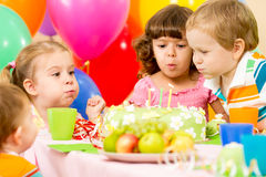 Os miúdos comemoram velas de sopro do aniversário no bolo foto de stock