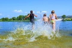 Os miúdos funcionam na água Fotografia de Stock Royalty Free