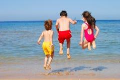 Os miúdos que saltam na praia fotografia de stock