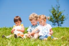 Os miúdos sentam-se na grama Foto de Stock Royalty Free