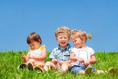 Os miúdos sentam-se na grama Fotografia de Stock Royalty Free