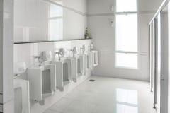 Os mictórios brancos na sala limpa do toalete público dos homens esvaziam Fotos de Stock Royalty Free