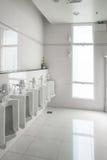 Os mictórios brancos na sala limpa do toalete público dos homens esvaziam Fotografia de Stock Royalty Free