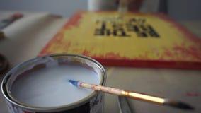 Os ?midos do artista a escova no frasco Cobre a imagem com o verniz Pinte latas Coworking of?cio vídeos de arquivo