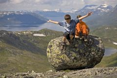 Os miúdos que saltam da pedra grande Foto de Stock Royalty Free