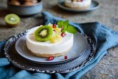 Os mini bolos de queijo Unbaked cobriram com abacaxi, quivi e romã fotos de stock