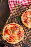 Os mini margheritas das pizzas serviram sobre em uma placa de madeira Parte traseira de madeira Foto de Stock