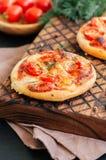 Os mini margheritas das pizzas serviram sobre em uma placa de madeira Parte traseira de madeira Fotos de Stock