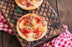 Os mini margheritas das pizzas serviram sobre em uma placa de madeira Parte traseira de madeira Fotografia de Stock Royalty Free