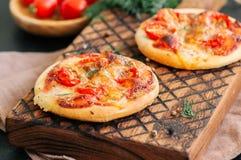 Os mini margheritas das pizzas serviram sobre em uma placa de madeira Pedra preta Imagem de Stock