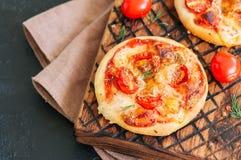Os mini margheritas das pizzas serviram sobre em uma placa de madeira Pedra preta Fotos de Stock