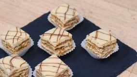 Os mini seis bolos em uma placa preta quadrada gerenciem em torno de sua linha central, pastelarias doces minúsculas das mostras  filme