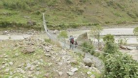 Os mochileiros andam na ponte de suspensão sobre o rio em Nepal Passeio na montanha do circuito de Manaslu video estoque