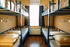 Os mochileiros ficam no hotel com as camas modernas do ?nibus de dois andares dentro da sala do dormit?rio para doze povos imagens de stock