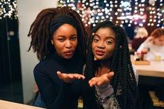 Os modelos africanos atrativos e bonitos olham retos e enviam beijos Sorriem e sentam-se junto As jovens mulheres olham imagem de stock royalty free