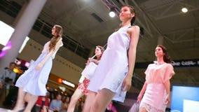 Os modelos nos vestidos andam ao longo do pódio no desfile de moda video estoque