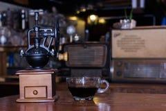 Os moedores de café e os copos de café preto estão na tabela fotos de stock