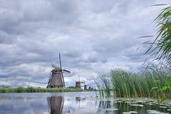 Os moinhos de vento com as nuvens dadas forma dramáticas refletiram em um canal, Foto de Stock