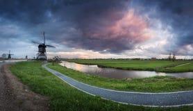 Os moinhos de vento holandeses tradicionais aproximam canais da água com céu nebuloso, paisagem Foto de Stock