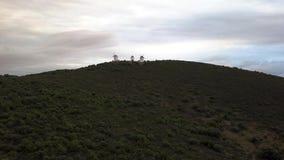Os moinhos de vento de visita em uma montanha cobrem no por do sol filme