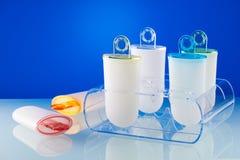 Os moldes plásticos do formulário do lolly do gelado estão no suporte de plexiglás fotos de stock