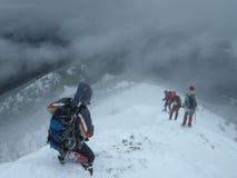 Os montanhistas entram no abismo nevado escuro Fotos de Stock