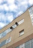 Os montanhistas industriais lavam janelas em uma construção de alto cargo Foto de Stock Royalty Free