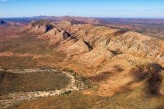 Os montes áridos e secam creekbed no MacDonnells ocidental Fotografia de Stock