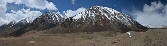 Os montes marrons enormes, partes superiores são cobertos com a neve, estiramento na distância com uma corrente de montanha longa Fotografia de Stock