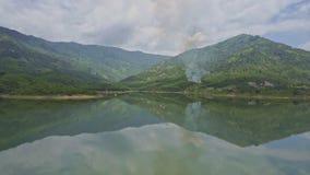 Os montes verdes com fumo do fogo refletem na superfície do lago do espelho filme