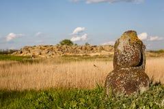 Os monumentos históricos de Scythian chamaram os stelae kurgan que estão na natureza contra o céu azul com as nuvens na casa dour imagens de stock