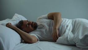 Os mosquitos irritantes que perturbam o homem na cama precisam redes do repelente de insetos e da janela video estoque