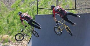 Os motociclistas de Bmx saltam em tandem fotos de stock royalty free