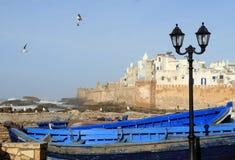 Os muralhas de Essaouira veem com a lanterna e o navio azul tradicional em Essaouira, Marrocos Essaouira ? uma cidade no ocidenta fotografia de stock royalty free