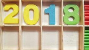 Os números coloridos nas pilhas de madeira formam o número 2018 Fotografia de Stock