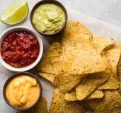Os nachos mexicanos lascam-se com molho da salsa, molho do molho de queijo e do guacamole e fatia do cal Fotografia de Stock