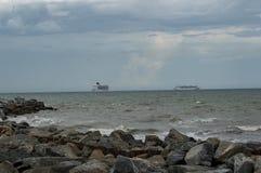Os navios de cruzeiros que dirigem para fora ao mar em um dia tormentoso imagem de stock