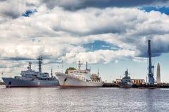 Os navios de guerra do russo e o almirante oceanográfico Vladimirsky da embarcação de pesquisa estão no porto médio gavan de Sred foto de stock royalty free