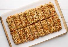 Os nenhuns caseiros cozem barras de granola com flocos da aveia, mel, os abricós secados e as sementes no papel branco do cozimen fotografia de stock royalty free