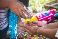 Os netos derramam a água nas mãos de pessoas idosas honradas Fotografia de Stock