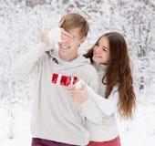 Os noivos da coberta da menina eyes com mãos e doação de um presente Imagem de Stock