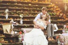 Os noivos em um estilo rústico que senta-se nas etapas de pedra na floresta ensolarada do outono, cercada pela decoração do casam foto de stock royalty free