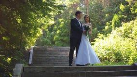 Os noivos estão andando ao longo da aleia do parque filme