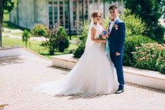 Os noivos estão andando ao longo do parque verde O par graceja no sorriso, aprecia um bom dia e um tempo morno A Foto de Stock Royalty Free